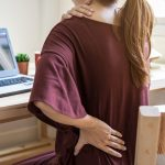 woman holding neck and back due to pain